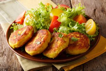 Serving fresh Ecuadorian potato pancakes with fresh vegetable salad close-up on a plate. horizontal