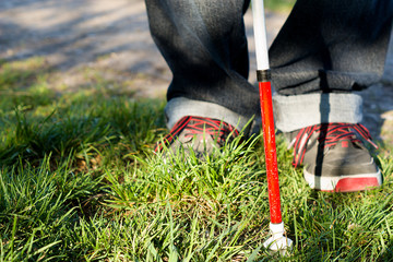 a isolated blind stick, cane in the foreground, blurred shoes in the background