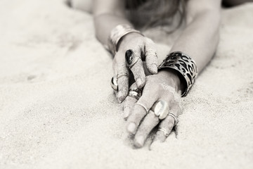 Artistic photo of female hands with jewelry covered with sand grains