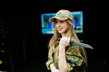 Military girl in camouflage uniform with knife at hand against army background on shooting range.