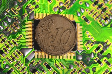 Euro 10 cent coin on circuit board.