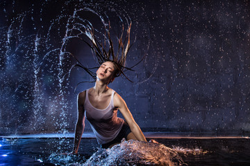 Girl with long hair during photoshoot with water in photo studio