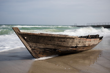the sea covers the waves with an old boat on the shore