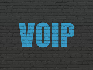 Web design concept: Painted blue text VOIP on Black Brick wall background