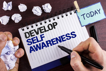 Text sign showing Develop Self Awareness. Conceptual photo improve your Informations about surrounding events written by Man on Notepad holding Marker on wooden background Crumpled Paper Balls