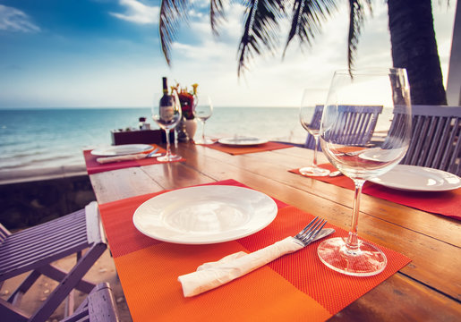 A romantic dinner in summer on a beach at sunset with two glasses of wine