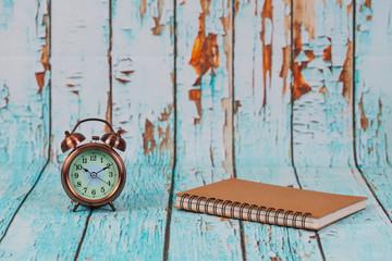old alarm clock on old wood background.