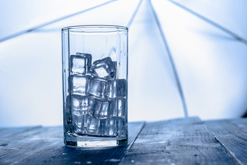 Glass of Ice cube on blue wooden table background.