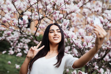 Beautiful stylish caucasian woman making selfie in blossom magnolia garden.