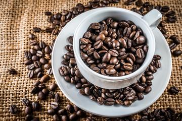 full coffee beans in white coffee cup win burlap background