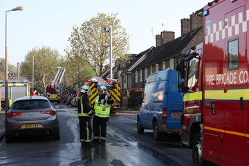 Firefighters stand on the street at the scene of a large fire in a residential care home  in Connington Crescent, Chingford, north-east London