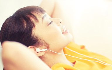 people, technology, relax and leisure concept - happy asian young woman lying on sofa with earphones listening to music at home