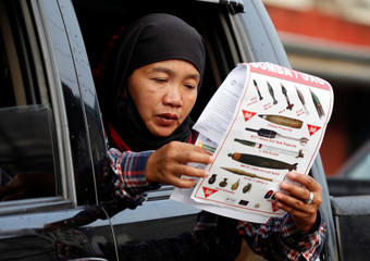 A woman reads a document at a military checkpoint before residents were allowed to return to their homes for the first time since the battle between government troops and Islamic State militants began in May last year, in the Islamic city of Marawi