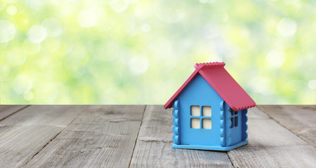 Small wooden house on blurred nature background.