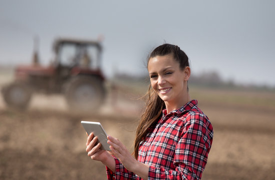 Farmer woman with tablet and tractor in field