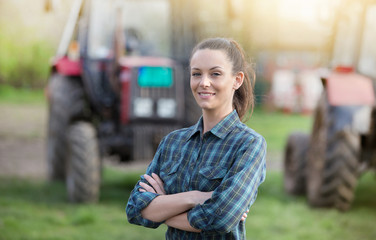 Farmer woman with tractors on farmland