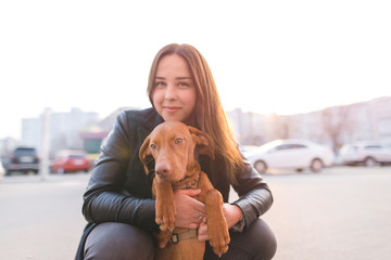 Portrait of a dog and a girl's owner against the background of the sunset. A walk with a pet in the city. The breed is Magyar Vizsla and the girl. The girl hugs a puppy. Magyar Vizsla Breed.