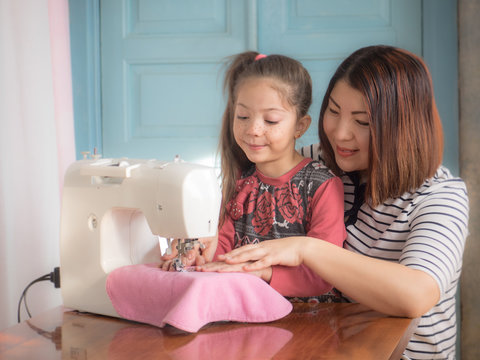 mom teaches her daughter to sew on a sewing machine
