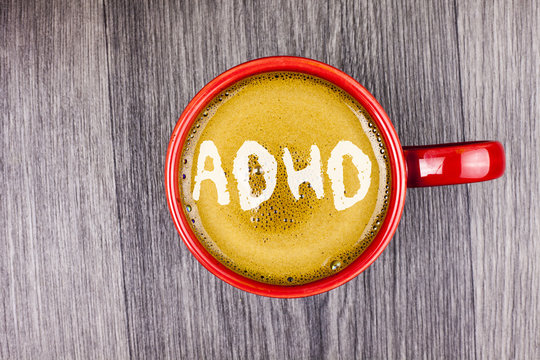 Conceptual hand writing showing Adhd. Business photo text Learning made easier for children teaching no more a difficult task written on Coffee in Red Cup on Grey wooden background. Top view.