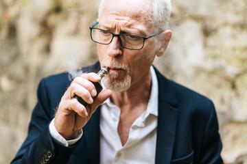 Mature man smoking electronic cigarette