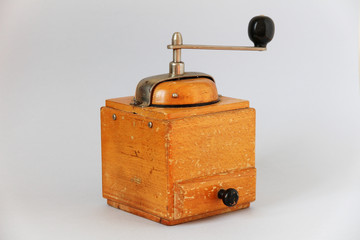 vintage old wooden coffee grinder. manual grinding. light background