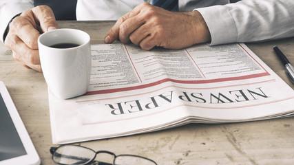 Businessman reading newspaper on workplace