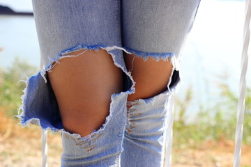 Knees of a girl in torn blue jeans. Feet trendy girl in torn blue jeans. Teenager and fashion. Clothes for young people. Clothing for teenagers. Slender girl in stylish denim pants with holes