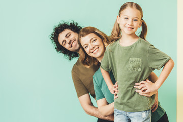 happy parents with cute little daughter wearing t-shirts and smiling at camera