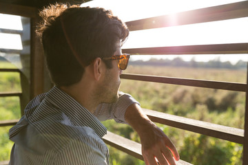 Man looking to nature from observation post at sunset