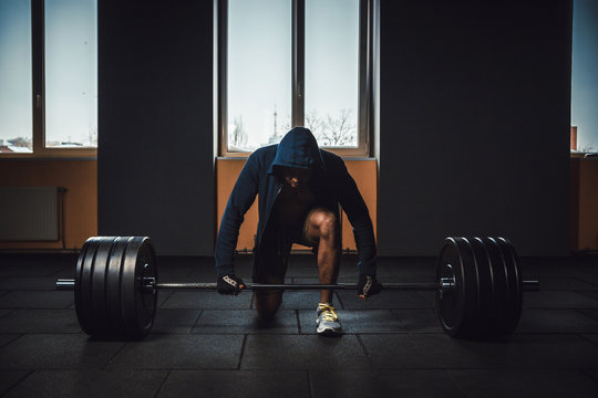 athletic man in jacket with a hood waiting and preparing before lifting heavy barbell. fitness, sport, training, gym and lifestyle concept. deadlift with barbell in mask. bent over the barbell