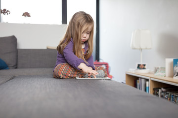 Little girl sitting on sofa in living room playing game on digital tablet