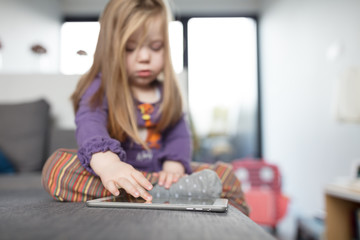 Child at home sitting on sofa, playing with tablet