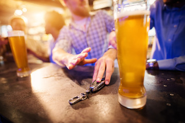Drunk man taking car key from pub table with a draft beer in front. Close up focus view of key and hands.