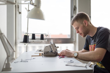 Young man sewing clothes in fashion design studio