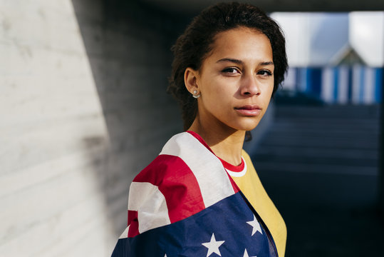 Portrait of young woman standing with American flag