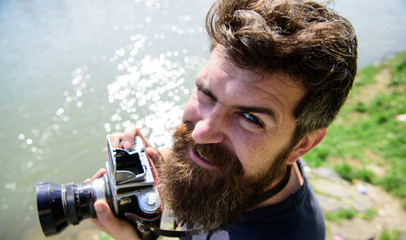 Man with beard holds photocamera on nature background. Photographer holds retro camera. Hipster on smiling face holds old fashioned camera. Photographer concept. Guy shooting nature near river.