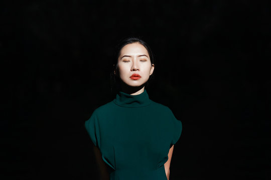 Woman with eyes closed standing against black background