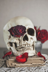 Still life with dry red roses and skull on vintage book