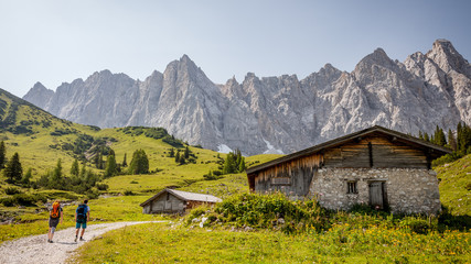 hiking in alpenpark karwendel austria with mountainscape background backpackers and house
