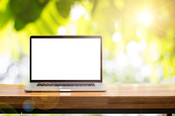 Laptop blank screen on wooden table in green garden blurred background with lens flare
