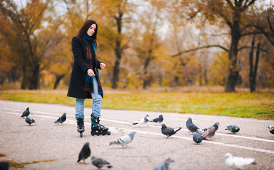 A young beautiful girl in a dark coat and blue jeans stands on roller skates in an autumn park and feeds doves.
