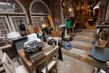 Old antique store with many vintage utensil, decor, wooden furniture, retro typewriter and many details