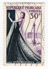 Leeds, England - April 20 2018: an old purple french postage stamp with an image of a woman in a dress celebrating fashion