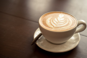 coffee cup latte art. Hot coffee cappuccino latte art. A Cup of hot latte art coffee on wooden table,