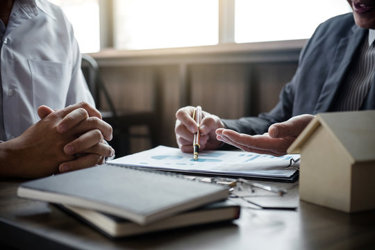 Real estate broker agent being analysis and making the decision a home estate loan to customer to signing contract documents for realty purchase, Bank employees recommend mortgage loan approval