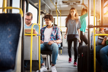Multicultural group of young people is traveling by bus.