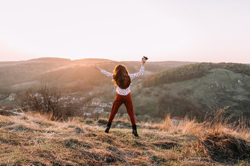 Portrait of girl with a binoculars on top of the mountains walking at sunset
