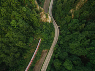 aerial view of road in beautiful mountain forest with train on railroad