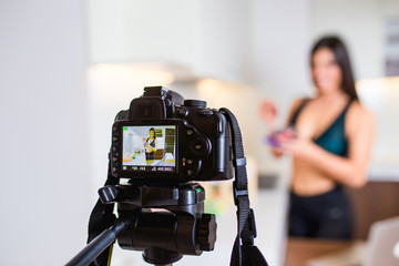 Young female vlogger recording content for her video blog. Fitness and healthy lifestyle concept. Freelance job.