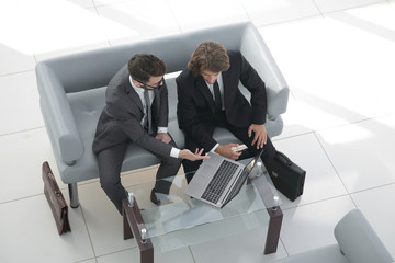 business colleagues discussing data from the laptop.